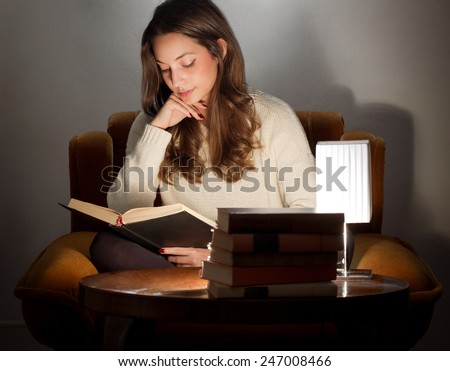 Portrait of brunette beauty reading books at home. - stock photo