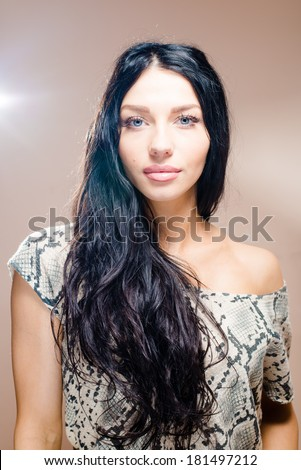 portrait of brunette casual woman with long black hair blue eyes gorgeous lips plump one bared shoulder, smiling & looking at camera on light brown background