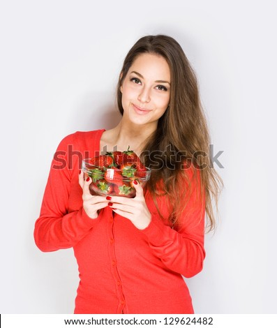Portrait of brunette cutie with bowl of juicy strawberries. - stock photo
