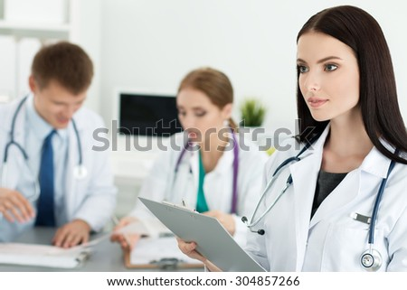 Portrait of brunette female medicine doctor holding document folder with two her colleagues working at background. Healthcare and medicine concept. - stock photo