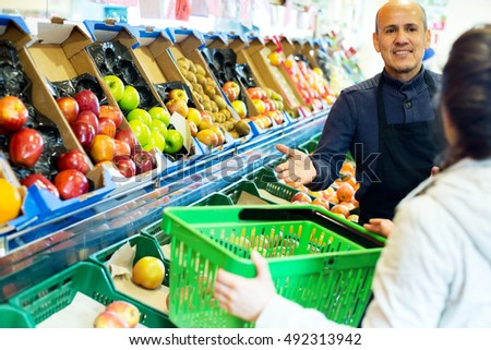 Portrait of brunette girl buying ripe fruits and smiling male seller in supermarket