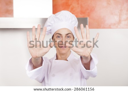 portrait of brunette happy chef woman with professional jacket and hat in white and orange kitchen showing both open palms of hands