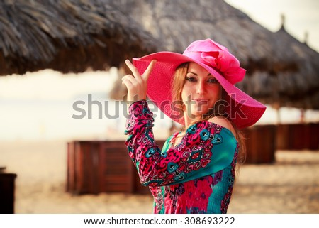 portrait of brunette longhaired girl in big red hat touching hat and smiling against defocused reed umbrella - stock photo