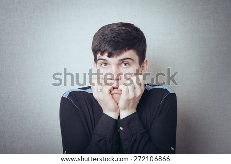 portrait of brunette man scared and keeps finger in mouth