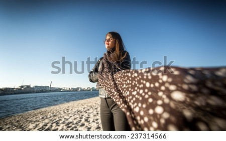 Portrait of brunette woman in scarf posing on beach at windy day - stock photo