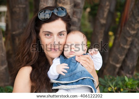 portrait of brunette woman mother grey shirt with two month age baby with blue jeans dress and white onesie embraced in her hands and arms with natural background - stock photo