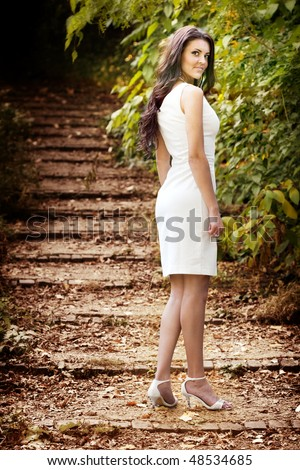 Portrait of brunette woman with sexy body and elegant dress