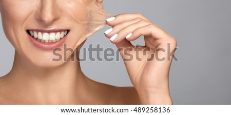 Portrait of brunette young Beautiful woman in facial peel off mask. Peeling. Beauty girl and body skin care. Isolated on grey background. Studio shot. Pull piece of leather to the side. Hand holding
