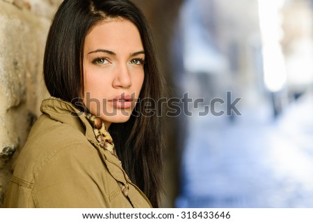 Portrait of brunette young woman with green eyes, wearing a coat, in urban background - stock photo