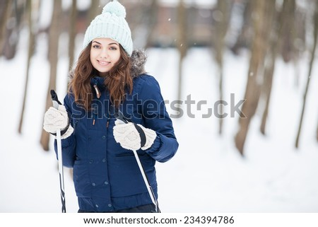 Portrait of Brunette young woman with ski in winter time - stock photo