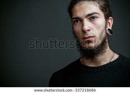 Portrait of brutal bearded man in blank t-shirt on black background