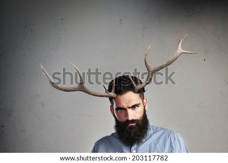 Portrait of brutal bearded man with horns - stock photo