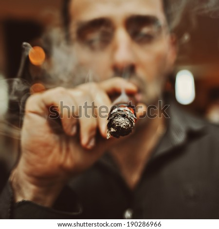 Portrait of brutal man with a cigar and smoke