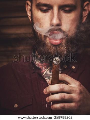 Portrait of brutal tattooed male smoking cigar - stock photo