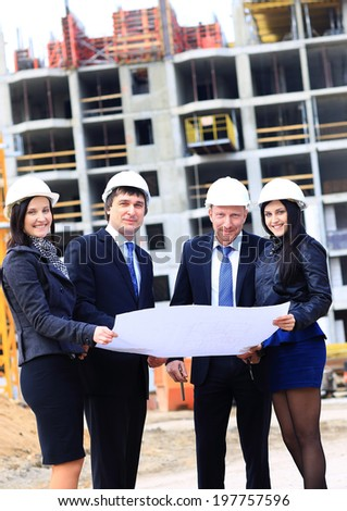 Portrait of builders standing at building site and discussing new project - stock photo