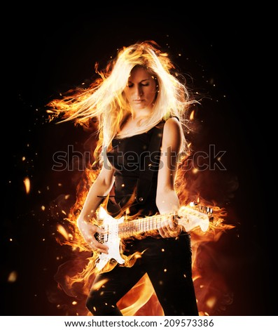 Portrait of burning young attractive blond woman playing on electric fire guitar - stock photo