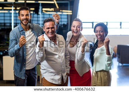 Portrait of business colleagues cheering with clenched fist in the office - stock photo