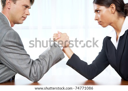 Portrait of business competitors doing arm wrestling and looking into each other?s eyes - stock photo