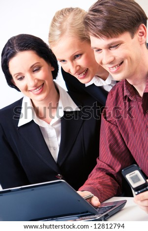 Portrait of business group looking at laptop screen with smiles while man pressing the keys