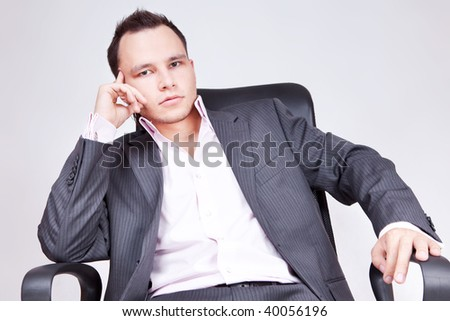 Portrait of business male model. Young businessman sitting on chair and thinking.