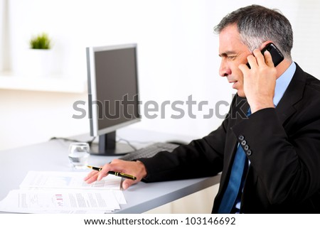 Portrait of business man conversing on mobile at the office - stock photo
