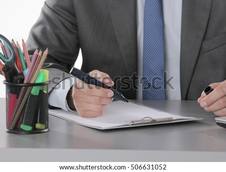 portrait of business man hand writing at notebook and holding mobilephone.