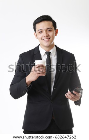 Portrait of business man isolated using mobile Phone and holding Coffee Cup
