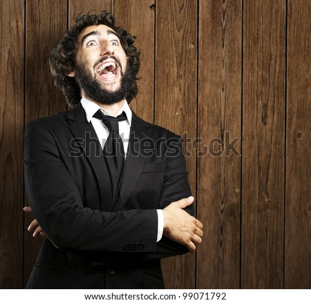 portrait of business man laughing against a wooden wall - stock photo