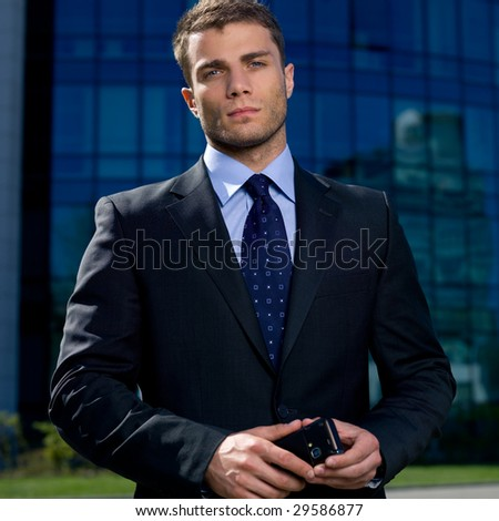 Portrait of business man outside the building using cell phone - stock photo