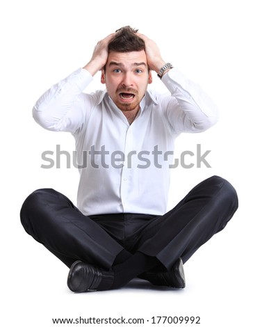 Portrait of business man sitting on the floor with shocked facial expression, isolated over white background - stock photo