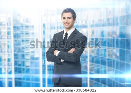 Portrait of business man with crossed hands on blue background. Concept of leadership and success - stock photo