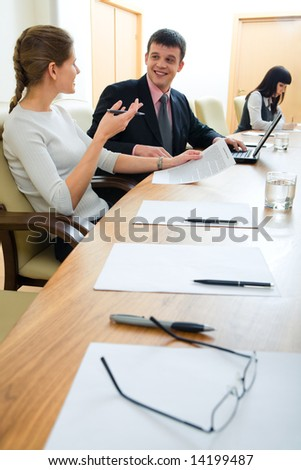 Portrait of business partners sitting in office and discussing their work on the background of working secretary