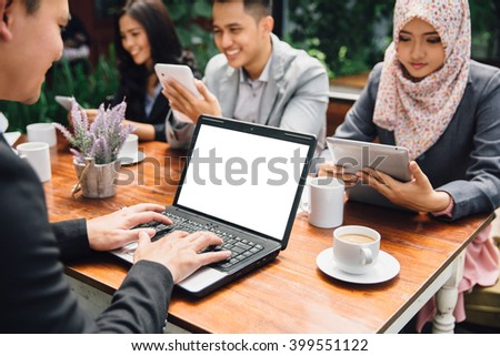 portrait of business people busy working with team at a cafe | focus on laptop - stock photo