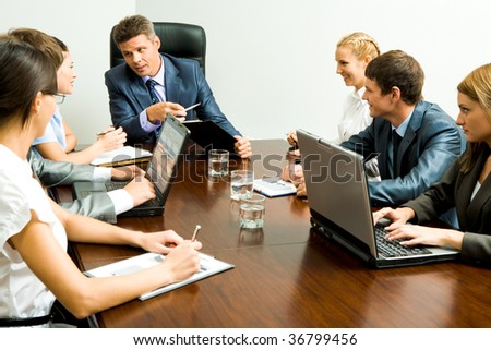 Portrait of business people communicating at working meeting - stock photo