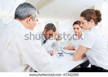 Portrait of business people deciding problems of project at meeting - stock photo