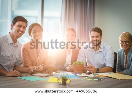 Portrait of business people discussing at desk in the office
