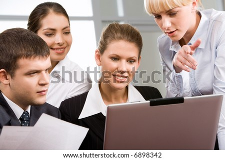 Portrait of business people gathered together around the laptop and discussing a new plan