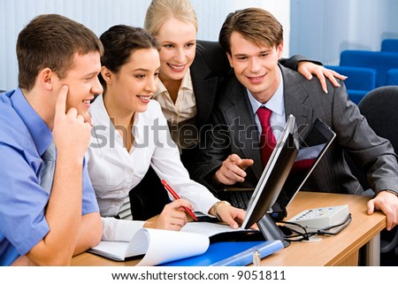 Portrait of business people looking at a monitor and discussing ideas - stock photo