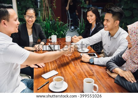 portrait of Business people shaking hands while having a lunch break at cafe - stock photo