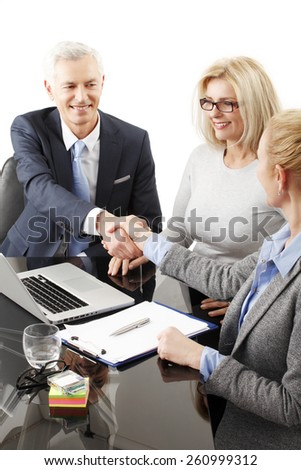 Portrait of business people shaking hands while sitting at business seminar. Isolated on white background.  - stock photo