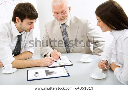Portrait of business people sitting around table and looking at document - stock photo