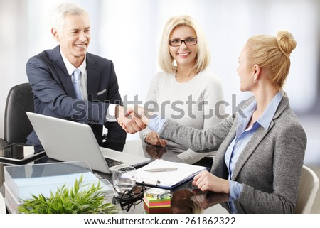 Portrait of business people sitting at desk and shaking hands.  - stock photo
