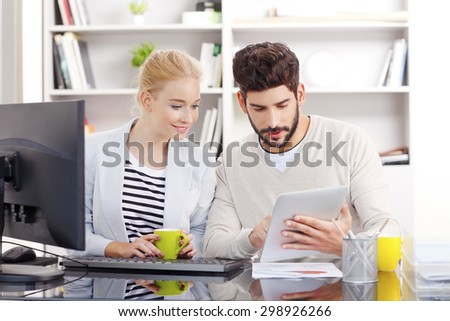Portrait of business people sitting at office in front of computer. Casual businesswoman and businessman working together. Young professional holding in handa digital tablet and touching the screen. - stock photo