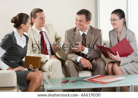 Portrait of business people sitting next to each other and communicating at business meeting - stock photo
