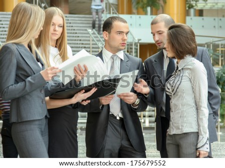 Portrait of  business people standing in the office looking into folder with business plan - stock photo