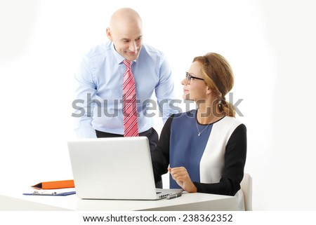 Portrait of business people working on presentation with laptop while sitting against white background. - stock photo