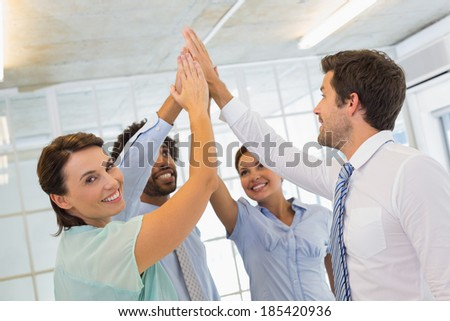 Portrait of business team joining hands together in the office - stock photo