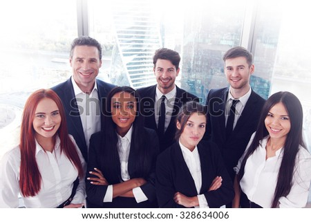 Portrait of business team of men and women in office with view on skyscrapers