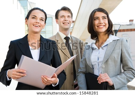 Portrait of business team outside looking straight and slightly upwards with smiles - stock photo
