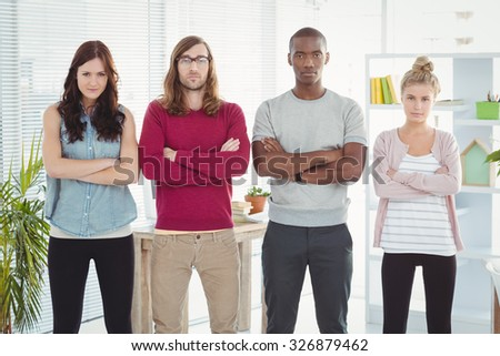 Portrait of business team with arms crossed while standing in a row at office - stock photo